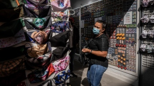 A woman checks face masks for sale at a shop in downtown Madrid, Spain, Monday, Sept. 21, 2020. (AP Photo/Bernat Armangue)