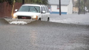 A vehicle drives through floodwaters from Tropical Storm Beta Tuesday, Sept. 22, 2020, in Galveston, Texas. Beta has weakened to a tropical depression as it parked itself over the Texas coast, raising concerns of extensive flooding in Houston and areas further inland. (Brett Coomer/Houston Chronicle via AP)
