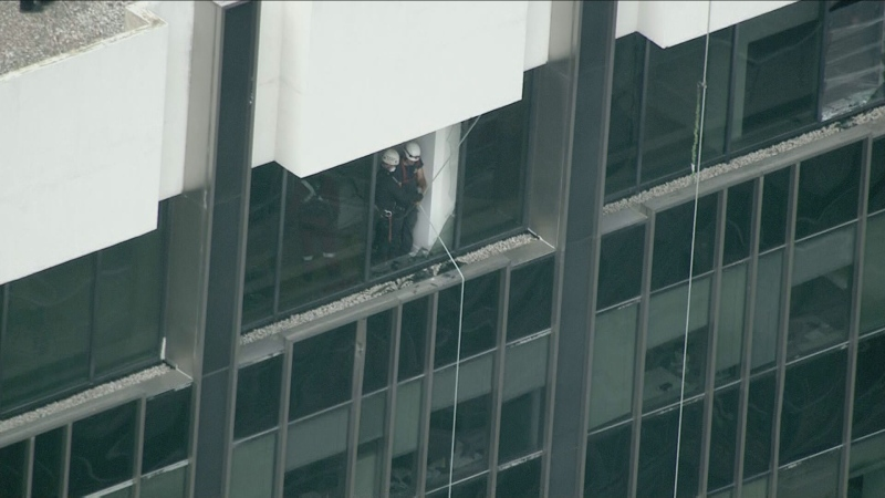Two workers are stuck on a ledge atop a high-rise in Midtown after the window washing platform they were on collapsed.