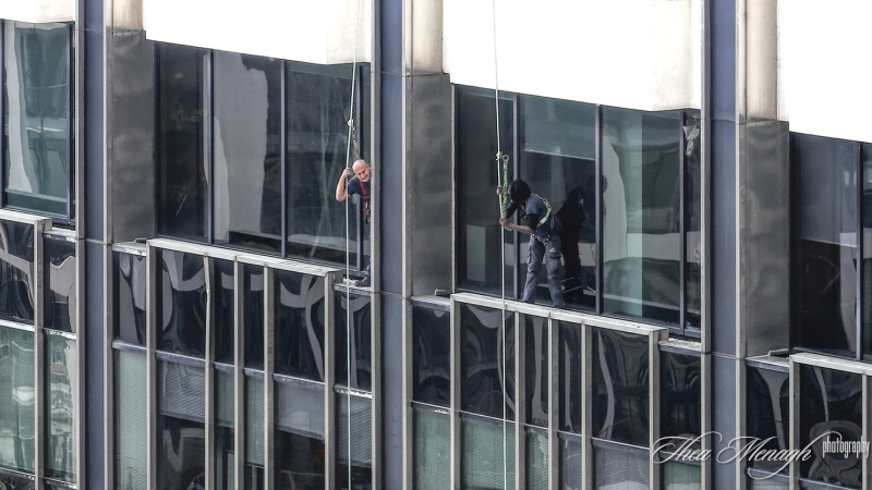 Two window washers wait to be rescued after their platform collapsed. (Photo courtesy of Thea Menagh)