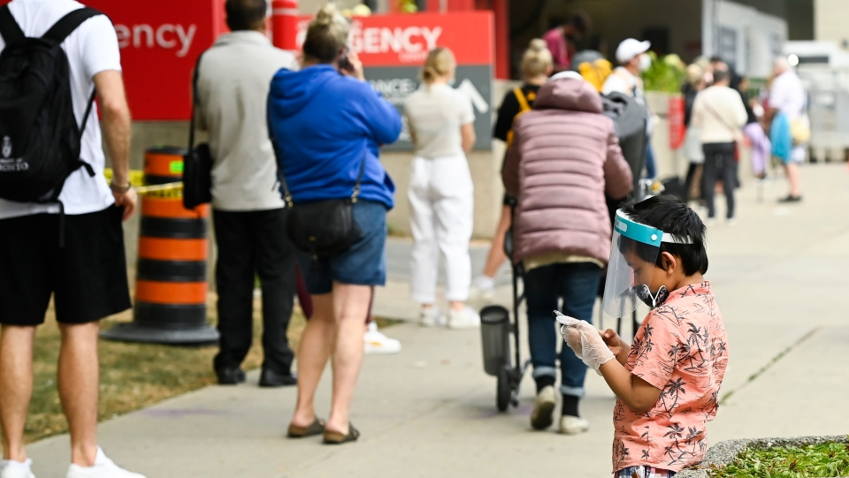 A young boy plays on a phone as he waits in line for hours at a COVID assessment centre at Mount Sinai Hospital during the COVID-19 pandemic in Toronto on Thursday, September 24, 2020. THE CANADIAN PRESS/Nathan Denette
