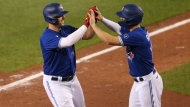 Toronto Blue Jays' Travis Shaw, left celebrates his two-run home run with teammate Randal Grichuk during the fourth inning of a baseball game against the Baltimore Orioles, Friday, Sept. 25, 2020, in Buffalo, N.Y. (AP Photo/Jeffrey T. Barnes)