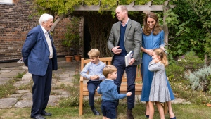 In this Thursday, Sept. 24, 2020 photo released by Kensington Palace, Britain's Prince William, centre, and Kate, the Duchess of Cambridge, react with Naturalist David Attenborough, left, with their children, Prince George, seated, Princess Charlotte, right and Prince Louis, foreground, in the gardens of Kensington Palace in London after Prince William joined Attenborough to watch a private outdoor screening of his upcoming film - David Attenborough: A Life On Our Planet. (Kensington Palace via AP)