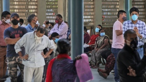 People wait for their results of  COVID-19 test at a government hospital in New Delhi, India, Monday, Sept. 28, 2020. India's confirmed coronavirus tally has reached 6 million cases, keeping the country second to the United States in number of reported cases since the pandemic began. (AP Photo/Manish Swarup)