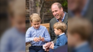 In this Thursday, Sept. 24, 2020 photo released by Kensington Palace, Britain's Prince William and Prince Louis react as Prince George holds the tooth of a giant shark given to him by Naturalist Sir David Attenborough in the gardens of Kensington Palace in London after Prince William joined Attenborough for an outdoor screening of his upcoming film - David Attenborough: A Life On Our Planet. (Kensington Palace via AP)