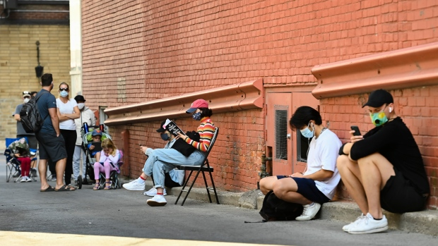 People sit in an alleyway for hours at a COVID assessment centre at St. Michael's Hospital during the COVID-19 pandemic in Toronto on Monday, September 28, 2020. THE CANADIAN PRESS/Nathan Denette