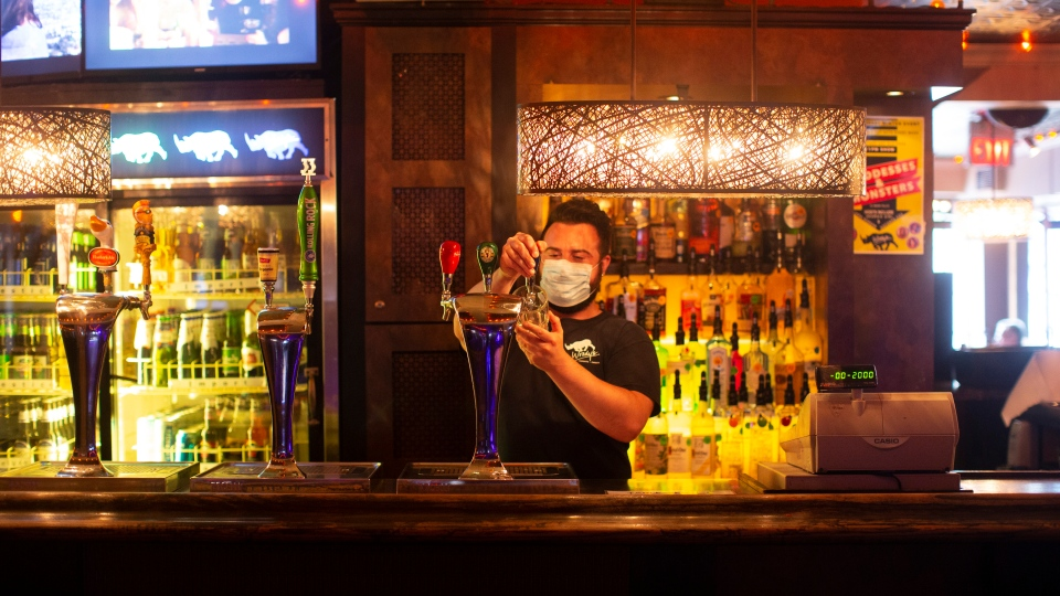 A bartender wears a mask at a bar in Toronto on Tuesday August 18, 2020. THE CANADIAN PRESS/Chris Young