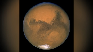 This Aug. 26, 2003 image made available by NASA shows Mars as it lines up with the Sun and the Earth. Photographed by the Hubble Space Telescope, it was about 55.8 million kilometers (34.6 million miles) from Earth. A network of salty ponds may be gurgling beneath Mars' South Pole alongside a large underground lake, raising the prospect of tiny, swimming Martian life. Italian scientists reported their findings Monday, Sept. 28, 2020 two years after identifying what they believed to be a large subglacial lake. (J. Bell/NASA via AP)