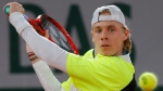 Canada's Denis Shapovalov plays a shot against France's Gilles Simon in the first round match of the French Open tennis tournament at the Roland Garros stadium in Paris, France, Tuesday, Sept. 29, 2020. (AP Photo/Michel Euler)