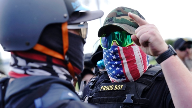 """In this Sept. 26, 2020 file photo, a right-wing demonstrator gestures toward a counter protester as members of the Proud Boys and other right-wing demonstrators rally in Portland, Ore. President Donald Trump didn't condemn white supremacist groups and their role in violence in some American cities this summer. Instead, he said the violence is a """"left-wing"""" problem and he told one far-right extremist group to """"stand back and stand by."""" His comments Tuesday night were in response to debate moderator Chris Wallace asking if he would condemn white supremacists and militia groups. Trump's exchange with Democrat Joe Biden left the extremist group Proud Boys celebrating what some of its members saw as tacit approval. (AP Photo/John Locher, File)"""