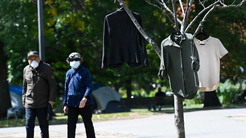People walk past a homeless person's clothes hanging on a tree to dry in Trinity Bellwoods Park during the COVID-19 pandemic in Toronto on Monday, September 21, 2020. THE CANADIAN PRESS/Nathan Denette