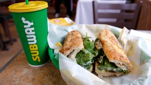 FILE - In this Friday, Feb. 23, 2018 file photo, the Subway logo is seen on a soft drink cup next to a sandwich at a restaurant in Londonderry, N.H.. Ireland's Supreme Court has ruled that bread sold by the fast food chain Subway contains so much sugar that it cannot be legally defined as bread. (AP Photo/Charles Krupa, File)