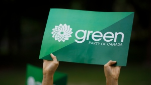 FILE - A supporter holds a sign for the Green Party of Canada in Toronto, Tuesday, Sept. 3, 2019. THE CANADIAN PRESS/Cole Burston