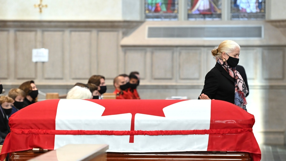 Elizabeth Turner, daughter of former Canadian prime minister John Turner, pats his casket on her way to speak during his state funeral service at St. Michael's Cathedral Basilica in Toronto on Tuesday, October 6, 2020. THE CANADIAN PRESS/Nathan Denette