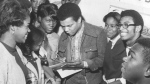 """Singer Johnny Nash signs autographs at a school in Houston on Nov. 27, 1969. The writer, singer and producer of the classic """"I Can See Clearly Now"""" has died. Nash's son says his father died Tuesday at his home in Houston of natural causes at 80. (Orie Collins./Houston Chronicle via AP)"""