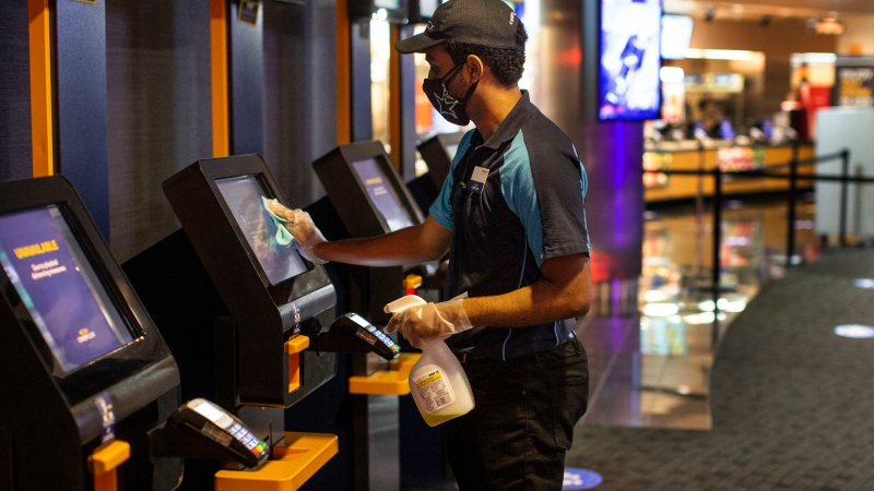 Cineplex employee wipes down a ticket touch screen at a theatre in Toronto as part of health and safety protocols put in place at Cineplex movie screens, due to the continued COVID19 pandemic, on Tuesday, October 6, 2020. THE CANADIAN PRESS/Chris Young