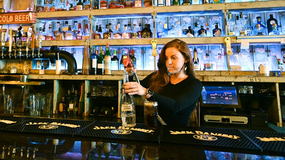 Bartender Victoria Colombe fills a drink for customers while working at Door Fifty Five bar and restaurant during the COVID-19 pandemic in the Port Credit neighbourhood of Mississauga, Ont., Friday, Oct. 9, 2020. THE CANADIAN PRESS/Nathan Denette