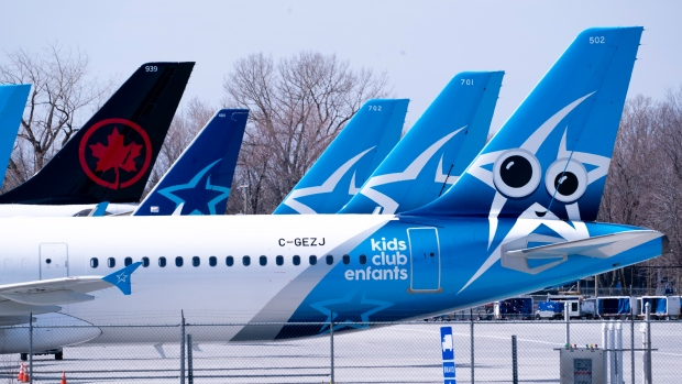 Tails of Air Transat and an Air Canada aircraft are seen on the tarmac at Montreal-Trudeau International Airport, in Montreal, Wednesday, April 8, 2020. THE CANADIAN PRESS/Paul Chiasson