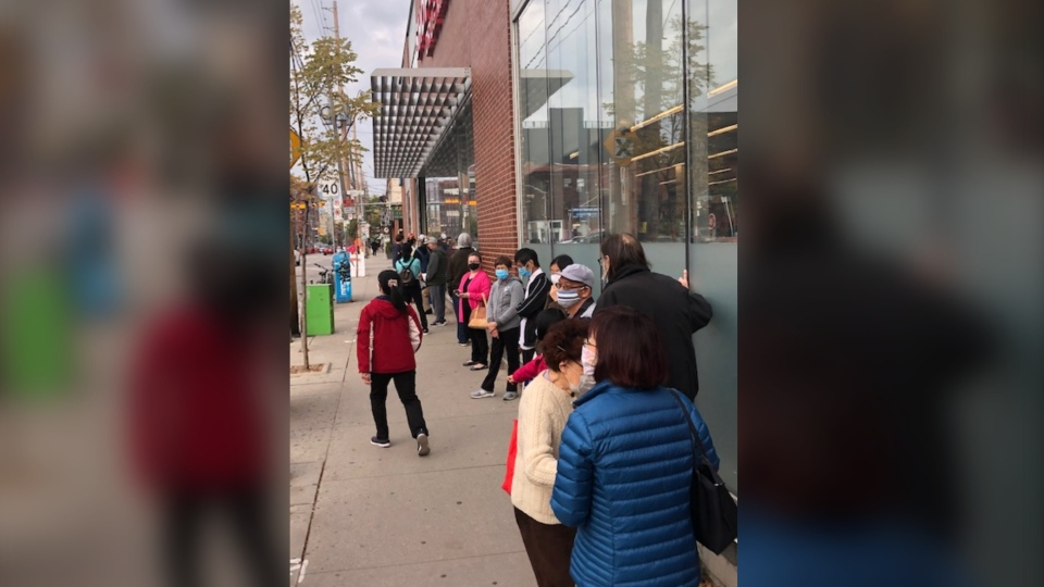 People are seen lining up outside of Shoppers Drug Mart at Queen Street and Carlaw Avenue in Toronto to get a flu shot. (CTV News/Peter Camp)