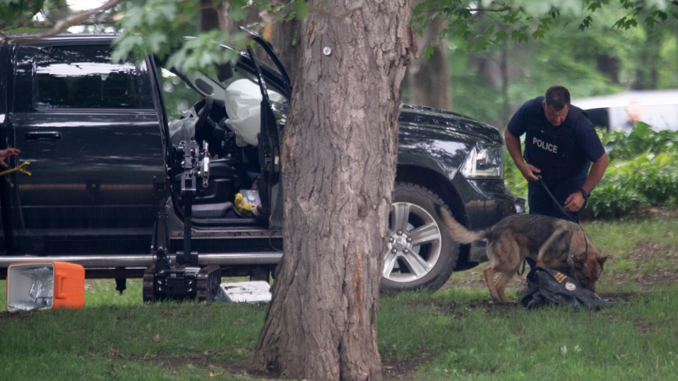 An RCMP officer works with a police dog as they move through the contents of a pick up truck on the grounds of Rideau Hall in Ottawa, Thursday, July 2, 2020. The man accused of threatening Prime Minister Justin Trudeau in the Rideau Hall incident will appear in court next month. THE CANADIAN PRESS/Adrian Wyld
