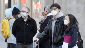 People wear face masks as they walk along a street in Montreal, Saturday, October 17, 2020, as the COVID-19 pandemic continues in Canada and around the world. THE CANADIAN PRESS/Graham Hughes