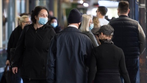 People wear face masks as they walk through a market in Montreal, Sunday, Oct. 18, 2020, as the COVID-19 pandemic continues in Canada and around the world. THE CANADIAN PRESS/Graham Hughes