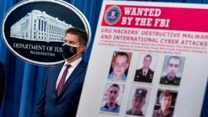 A poster showing six wanted Russian military intelligence officers is displayed as FBI Deputy Director David Bowdich appears for a news conference at the Department of Justice, Monday, Oct. 19, 2020, in Washington. (AP Photo/Andrew Harnik, pool)