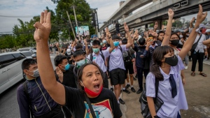 Pro-democracy protesters flash three-fingered salute during a demonstration at Kaset intersection, suburbs of Bangkok, Thailand, Monday, Oct. 19, 2020. (AP Photo/Sakchai Lalit)
