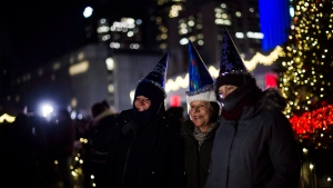 People take photographs in front of the Christmas tree after marking the beginning 2018 during New Years Eve celebrations held at Nathan Phillips Square in Toronto, Monday, Jan 1, 2018. THE CANADIAN PRESS/Christopher Katsarov