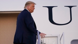 President Donald Trump stands at the top of the steps of Air Force One at Andrews Air Force Base, Md., Tuesday, Oct. 20, 2020. Trump is heading to Erie, Pa., for a campaign rally. (AP Photo/Susan Walsh)