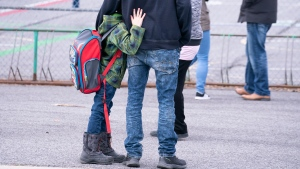 A young boy hugs his father as he waits to be called to enter the school yard the Marie-Derome School in Saint-Jean-sur-Richelieu, Que., Monday, May 11, 2020. THE CANADIAN PRESS/Paul Chiasson