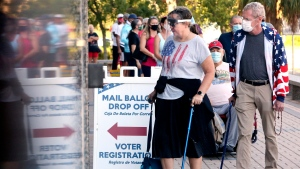 In this Monday, Oct. 19, 2020, file photo, voters Jenny Hart, center, and James Hart, of Clearwater, wait in line to enter the Supervisor of Elections Office at the Pinellas County Courthouse during early voting in Clearwater, Fla. (Douglas R. Clifford/Tampa Bay Times via AP, File)