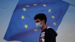 Backdropped by a poster with a European Union flag, a youth wearing a mask to help protect against the spread of coronavirus walks in Istanbul, Friday, Oct. 2, 2020. THE CANADIAN PRSS/AP/Emrah Gurel