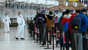 People line up and check in for an international flight at Pearson International airport during the COVID-19 pandemic in Toronto on Wednesday, Oct. 14, 2020. THE CANADIAN PRESS/Nathan Denette