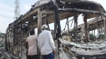 People inspect burnt out government transportation buses at the Berger station near Ikeja, Lagos, Nigeria, Thursday, Oct. 22, 2020. (AP Photo)