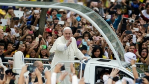 In this Jan. 18, 2015, file photo, crowds cheer as Pope Francis passes by during his meeting with the youth at the University of Santo Tomas in Manila, Philippines. (AP Photo/Aaron Favila, File)