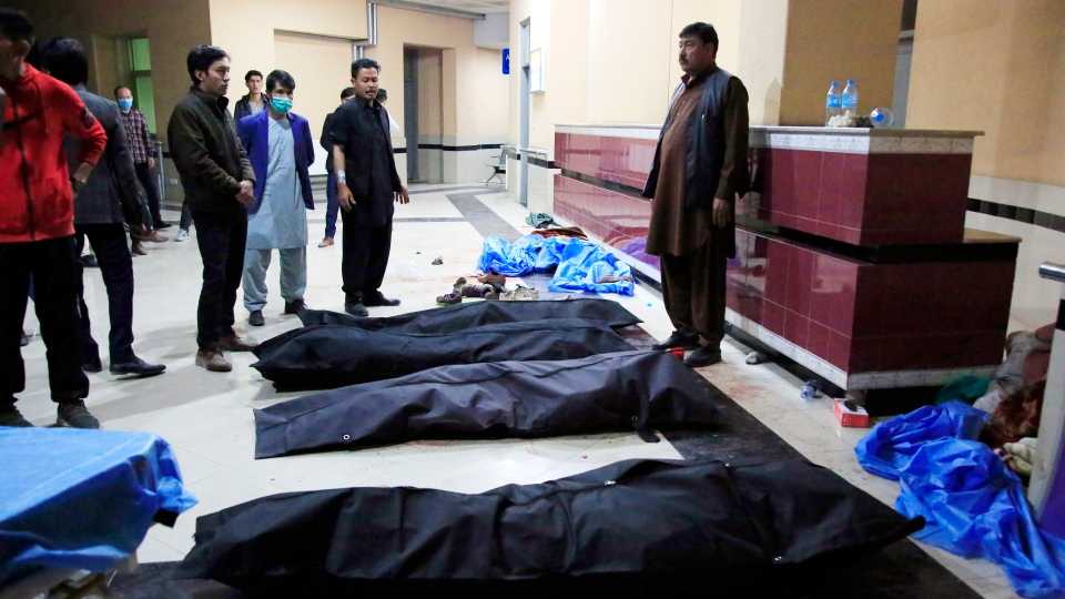 Afghan men look for their relatives at a hospital after a suicide attack in Kabul, Afghanistan, Saturday, Oct. 24, 2020. The death toll from the suicide attack Saturday in Afghanistan's capital has risen that includes schoolchildren, the interior ministry said.. (AP Photo/Mariam Zuhaib)