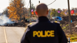Ontario Provincial Police look over a blockade on McKenzie Rd. in Caledonia, Ont., after a judge granted a permanent injunction against a land reclamation camp known as 1492 Land Back Lane Friday, October 23, 2020. THE CANADIAN PRESS/Tara Walton
