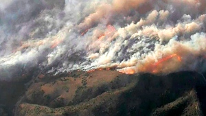 In this image from video provided by KNBC-TV, smoke and flames from the Silverado fire threatens areas near Irvine, Calif., Monday, Oct. 26, 2020. The fast-moving wildfire has forced evacuations for 60,000 people in Southern California as powerful winds across the state prompted power to be cut to hundreds of thousands to prevent utility equipment from sparking new blazes. (KNBC-TV via AP)