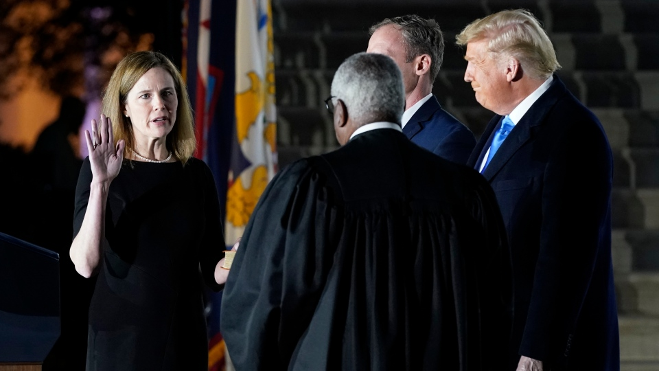 President Donald Trump watches as Supreme Court Justice Clarence Thomas administers the Constitutional Oath to Amy Coney Barrett on the South Lawn of the White House in Washington, Monday, Oct. 26, 2020, after Barrett was confirmed by the Senate earlier in the evening. (AP Photo/Patrick Semansky)