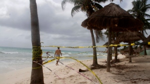 Tape closing off the beach blows in the wind before the arrival of Tropical Storm Zeta in Playa del Carmen, Mexico, Monday, Oct. 26, 2020. A strengthening Tropical Storm Zeta is expected to become a hurricane Monday as it heads toward the eastern end of Mexico's resort-dotted Yucatan Peninsula and then likely move on for a possible landfall on the central U.S. Gulf Coast at midweek. (AP Photo/Tomas Stargardter)