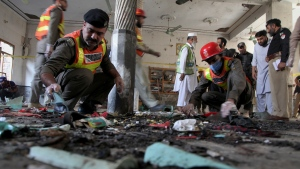 Pakistani rescue workers and police officers examine the site of a bomb explosion in an Islamic seminary, in Peshawar, Pakistan, Tuesday, Oct. 27, 2020. A powerful bomb blast ripped through the Islamic seminary on the outskirts of the northwest Pakistani city of Peshawar on Tuesday morning, killing some students and wounding dozens others, police and a hospital spokesman said. (AP Photo/Muhammad Sajjad)