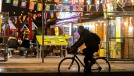 A cyclist rides past an open air world food market in Toronto on Monday October 26, 2020. Toronto has been allowing food and beverage business more latitude to open up outdoors to prevent the spread of COVID-19. THE CANADIAN PRESS/Frank Gunn
