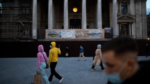 Passers-by, wearing face masks to prevent the spread of the coronavirus, walk past a clock installed at the La Bourse, former stock exchange, building during an autumn evening prior to the curfew in downtown Brussels, Friday, Oct. 23, 2020. (AP Photo/Francisco Seco)