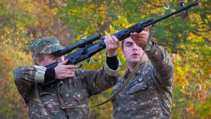 An instructor helps a volunteer soldier practice with a sniper rifle near a front line at a military base during a military conflict in the separatist region of Nagorno-Karabakh, Tuesday, Oct. 27, 2020. Fighting over Nagorno-Karabakh is raging, unimpeded by a U.S.-brokered cease-fire, while Armenia and Azerbaijan are trading blame for the deal's quick unraveling. (AP Photo)