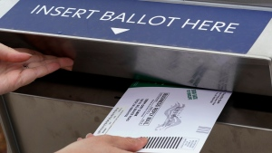 FILE - In this Thursday, Oct. 15, 2020, file photo, Nikki Schueller inserts her absentee voter ballot into a drop box in Troy, Mich. Just days before the presidential election, millions of mail-in ballots have still not been returned in key battleground states. Many of those are due in county offices by Tuesday, Nov. 3, but the latest Postal Service delivery data suggests it's too late for voters to drop their ballots in the mail. (AP Photo/Paul Sancya, File)