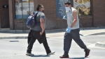 Migrant worker Omar Delgado Reyes, right (light grey shirt) of Mexico walks across Talbot St. in downtown Leamington, Ont., Tuesday, June 30, 2020 after doing some banking.The end of the month is pay day at many of the Leamington-area farms. THE CANADIAN PRESS/Rob Gurdebeke