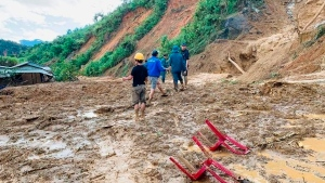Villagers wade through mud after a landslide swamps a village in Phuoc Loc district, Quang Nam province, Vietnam Thursday, Oct. 29, 2020. Three separated landslides triggered by Typhoon Molave killed more than a dozen villagers in the province as rescuers scramble to recover more victims. (Lai Minh Dong/VNA via AP)