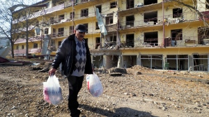 Vovik Zakharian, 72, walks past his apartment building damaged by shelling by Azerbaijan's forces during a military conflict in Shushi, outside Stepanakert, the separatist region of Nagorno-Karabakh, Thursday, Oct. 29, 2020. (AP Photo)