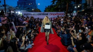 "Pro-democracy protesters perform on a mock ""red carpet"" fashion show billed as a counterpoint to a fashion show being held by one of the monarchy's princesses nearby in Bangkok, Thailand, Thursday, Oct. 29, 2020. (AP Photo/Gemunu Amarasinghe)"